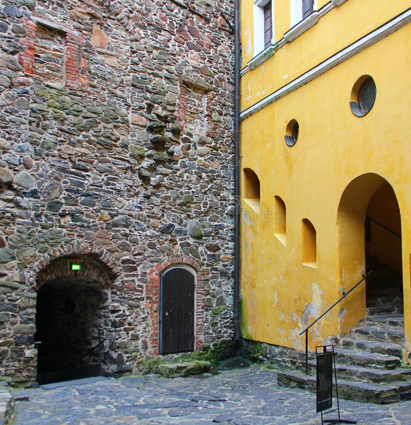 Two walls made in different styles. Two walls of the buildings touch each other, one stone of different sizes, the style of the middle ages, the passage in the royalty free stock photos