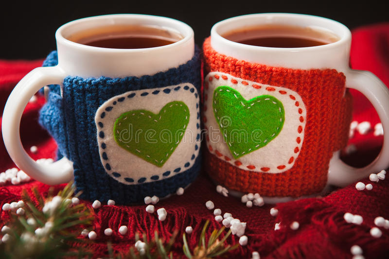Two warm cups of tea or coffee with heart for. Two warm cups of tea or coffee with red and blue knitted thing on it and with heart for Valentine's day royalty free stock photo