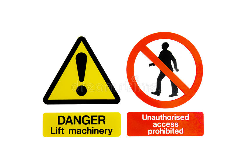 Two Warning Hazard Signs. Two isolated warning hazard signs, one of an exclamation mark on a yellow triangle for lift machinery, and one prohibiting unauthorised stock image