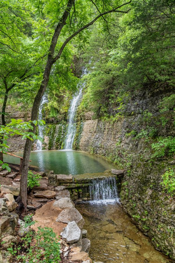 Two waterfalls cascading down the canyon walls into a reflection pond with summer foliage. And lined with stone stock photography