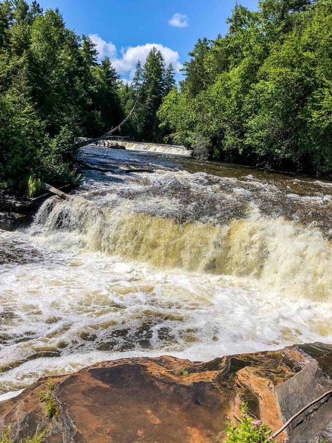 Two waterfalls cascading down rocks in Upper Michigan royalty free stock image