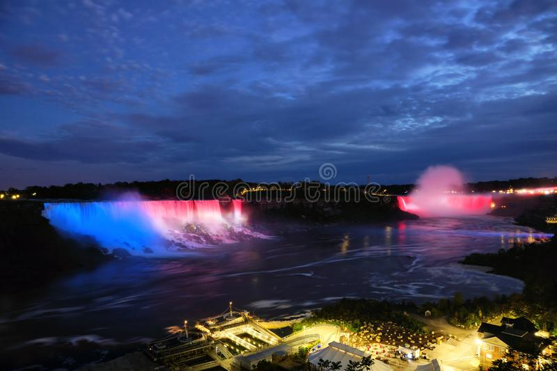 Niagara Falls colorfully lit at dusk, Ontario, Canada. The two waterfalls of Niagara Falls colorfully lit at dusk, Ontario, Canada stock images
