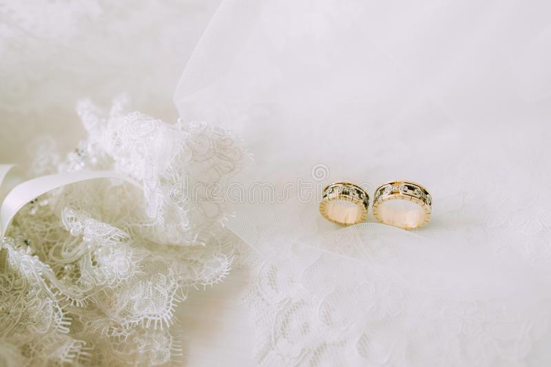 Two wedding gold rings on beautiful white tulle with lace garter close royalty free stock image