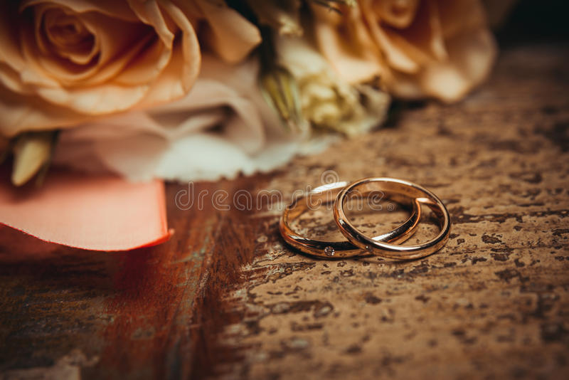 Two wedding rings and a bouquet of orange and white roses. royalty free stock photography