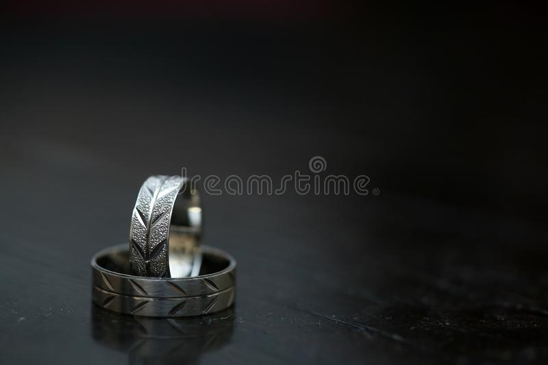 Two wedding rings on dark wooden surface with blurred background.  royalty free stock photos