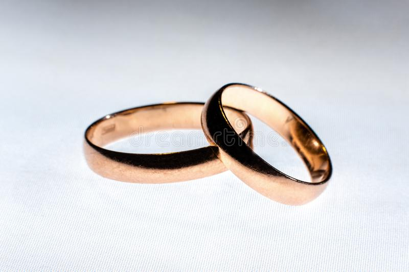 Two wedding rings of different sizes made in gold on the white light surface stock photo