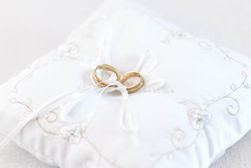 Two wedding rings on embroided white cushion. Two wedding rings on embroided white cushion, tied by white ribbon stock image