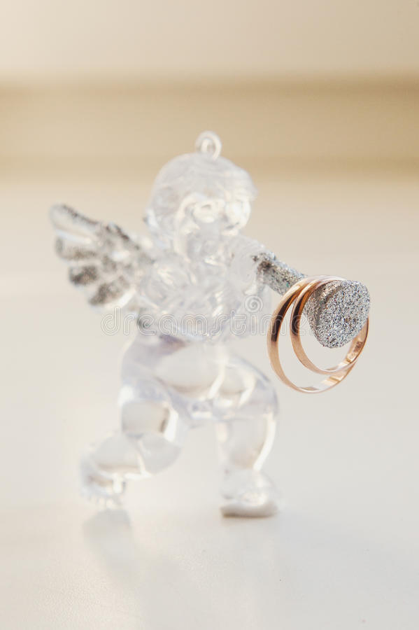 Two wedding rings on glass angel figurine. Macro royalty free stock photography