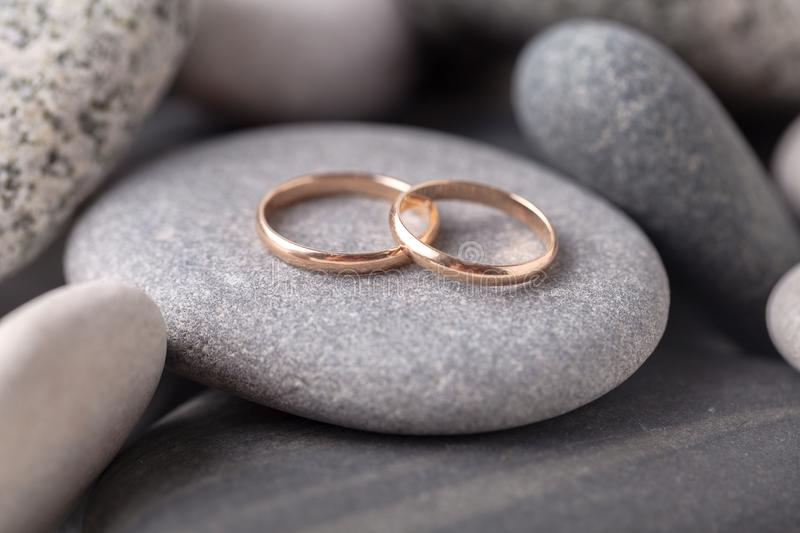 Two wedding rings lie on the sea rock royalty free stock photos