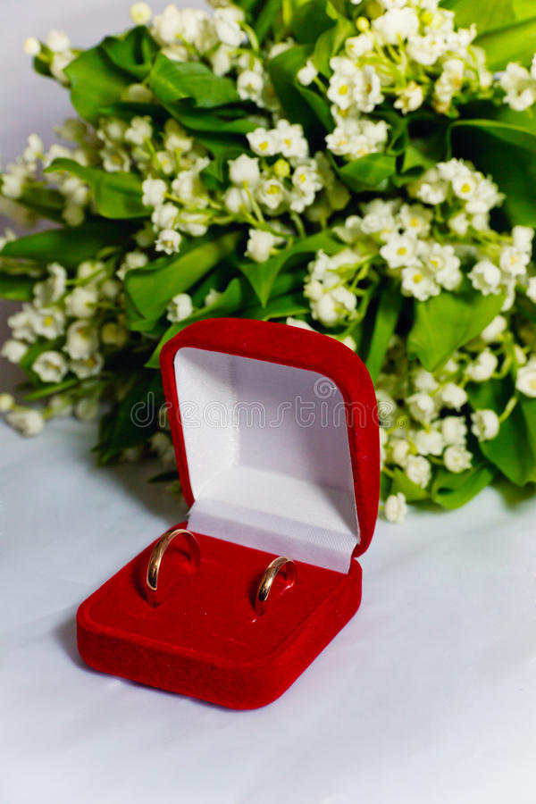 Two wedding rings and lilies of the valley royalty free stock photography
