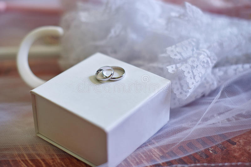 Two wedding rings made of white gold on box stock photo