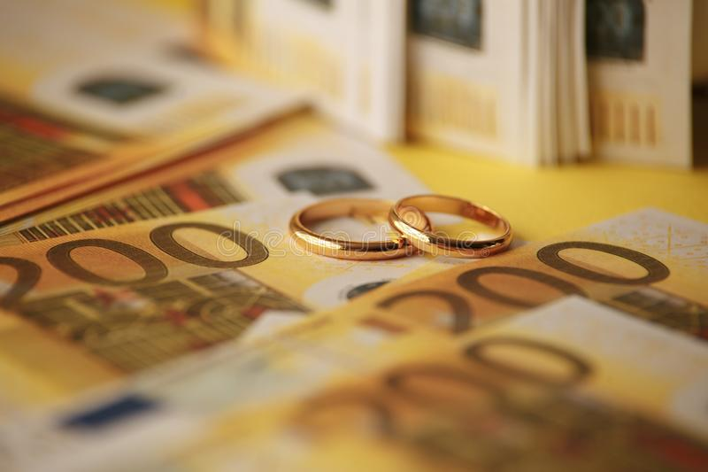 Two wedding rings and money as symbol for an expensive alliance. Golden wedding rings on euro banknotes stock photos