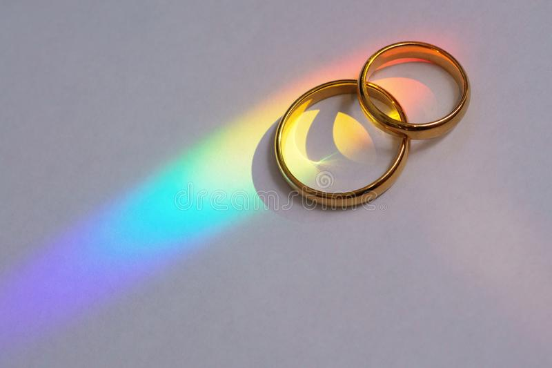 Two wedding rings with rainbow. Light royalty free stock photography