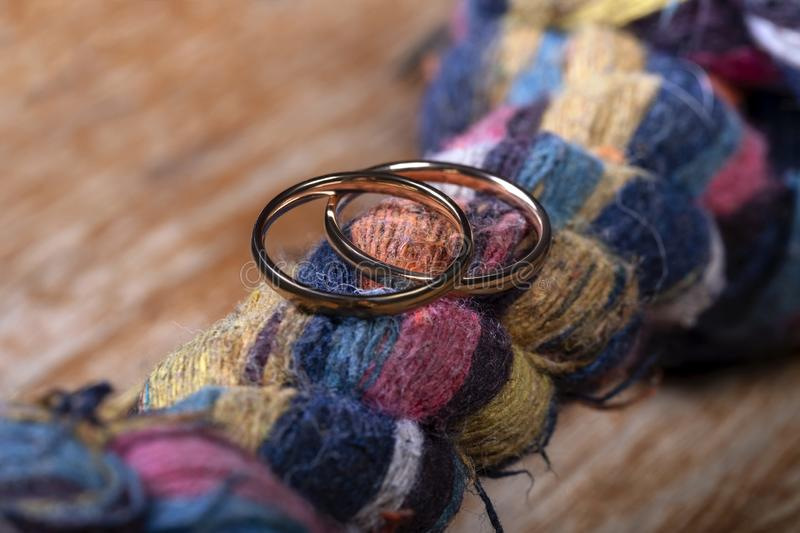 Two wedding rings on a rope knot and wood as a symbol of eternal love royalty free stock photos