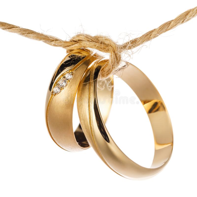 Two wedding rings tied with a rope as a symbol of the union of a new family, isolated royalty free stock images