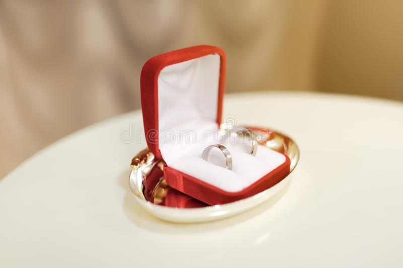 Two wedding rings on white pillow in red box during ceremony stock photos