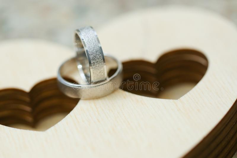 Two wedding rings on wooden case in heart shape. Close up macro shot of silver rings royalty free stock images