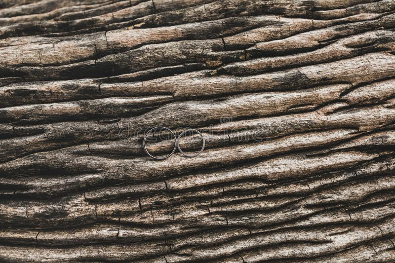 Two wedding rings on wooden texture background. Two wedding rings on wooden brown texture background close up royalty free stock photography