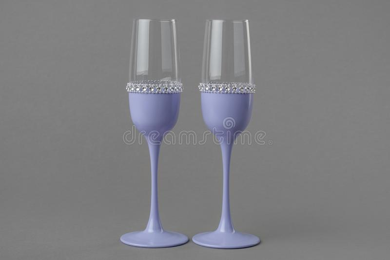 Two wedding wine glasses in lavender color. Two wedding wine glasses in lavender color on gray background royalty free stock photos