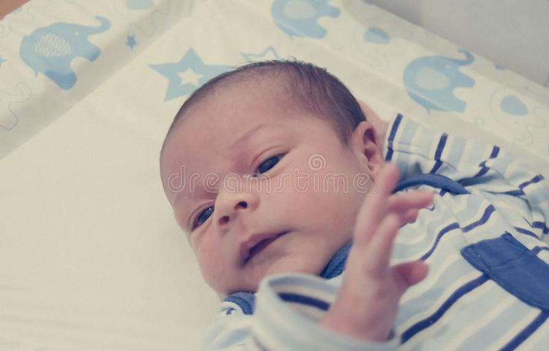 Two weeks old newborn baby boy sleeping on white sheet royalty free stock photography