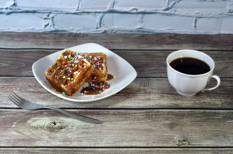 Two Wenk waffles topped with glazulu on a ceramic plate and a cup of black coffee on the table. Close-up royalty free stock photography