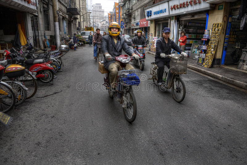 Two-wheeled motorized vehicles on a street in Shanghai, China. Shanghai, China - April 20, 2010: Traffic on the streets of Asian cities, two-wheeled transport stock photography