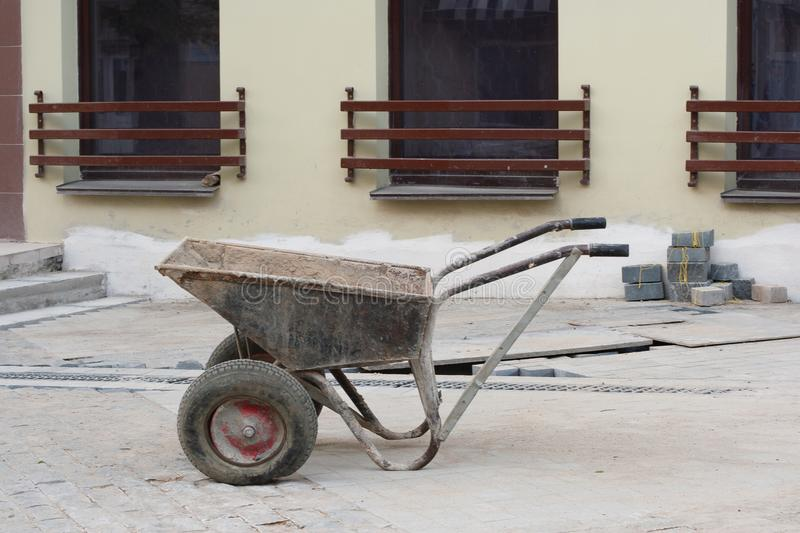 Two-wheeled wheelbarrow on a construction site of a granite pavement with grey regular and even stone blocks royalty free stock photos