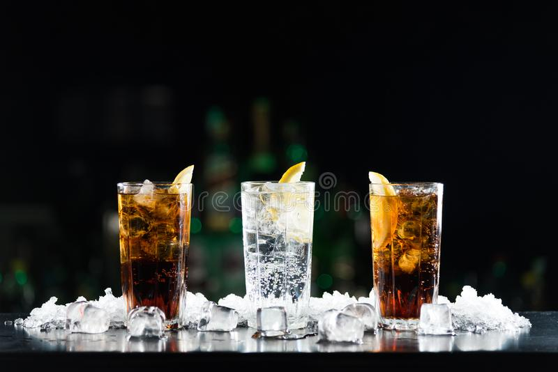 Two whisky and coke cocktails and one white alcoholic drink on the bar table. royalty free stock photo