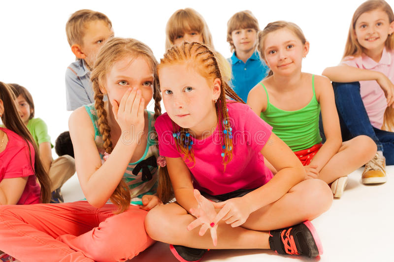 Two whispering girls sit among other friends stock image