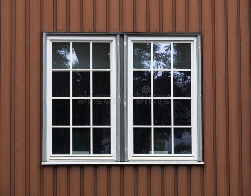 Two white adjacent large windows on a brown wood facade. Two white wood adjacent large windows on the  brown wood facade royalty free stock photography
