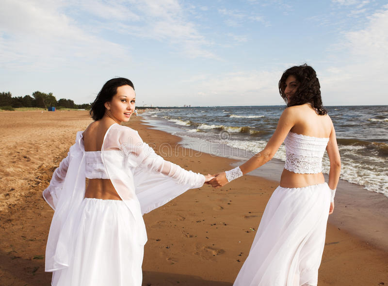 Two white angels on the beach. Two girls in white gown dansing on the seashore stock images