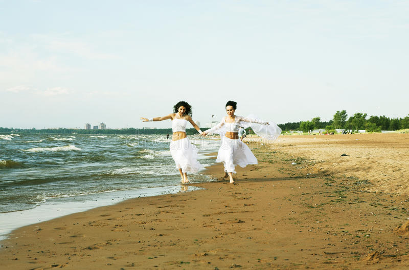 Two white angels on the beach. Two girls in white gown dansing on the seashore stock photos