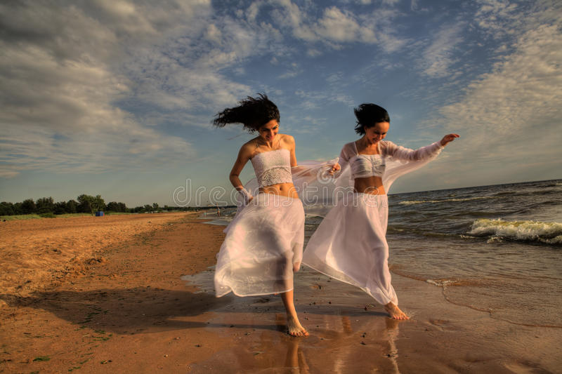 Two white angels on the beach. Two girls in white gown dansing on the seashore stock photography