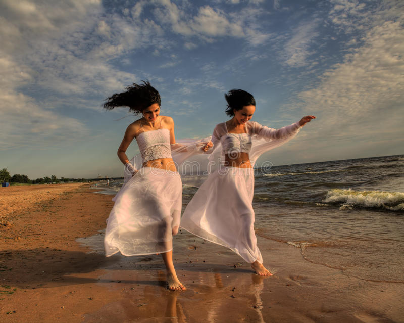 Two white angels on the beach. Two girls in white gown dansing on the seashore royalty free stock photography