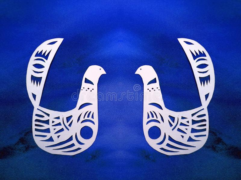 Two white birds cut from paper. Two beautiful birds cut from white paper on blue background royalty free stock image