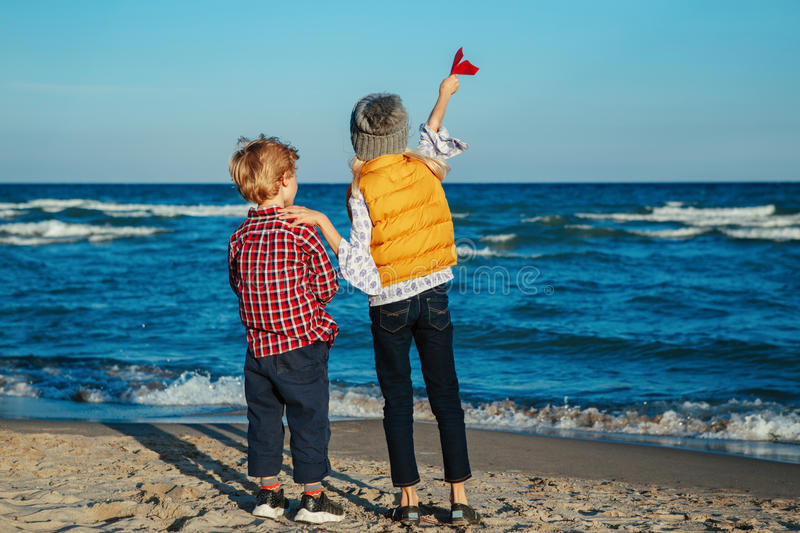Two white Caucasian children kids, older sister and younger brother playing paper planes on ocean sea beach on sunset royalty free stock photos