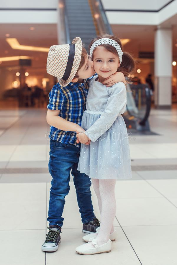 Two white Caucasian cute adorable funny children boy and girl hugging kissing. Group portrait of two white Caucasian cute adorable funny children boy and girl royalty free stock photos