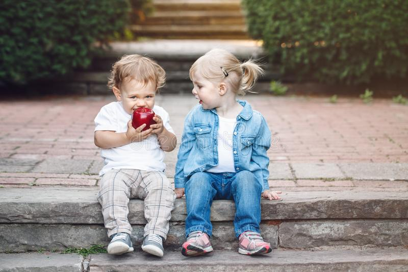 Two white Caucasian cute adorable funny children toddlers sitting together sharing eating apple food stock photos