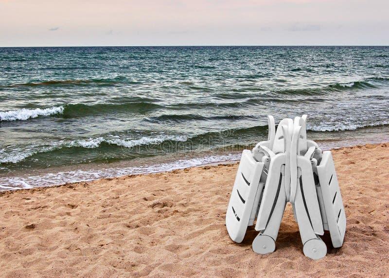 Two white chaise longue on sand on seashore. Beach. stock photos
