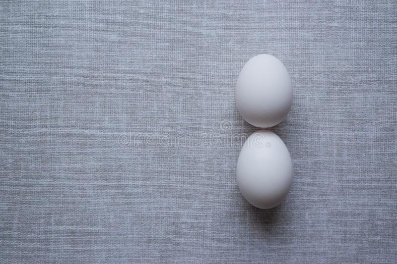Two white chicken eggs on a rough gray tablecloth. poor diet, poverty. lack of food, malnutrition. severe restrictions on food. Simple food. minimalistic top stock photos