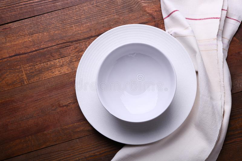 Two white clean plates on napkin. Two white clean plates on kitchen towel on wooden background. Concept table setting. Top view, copy space stock photo