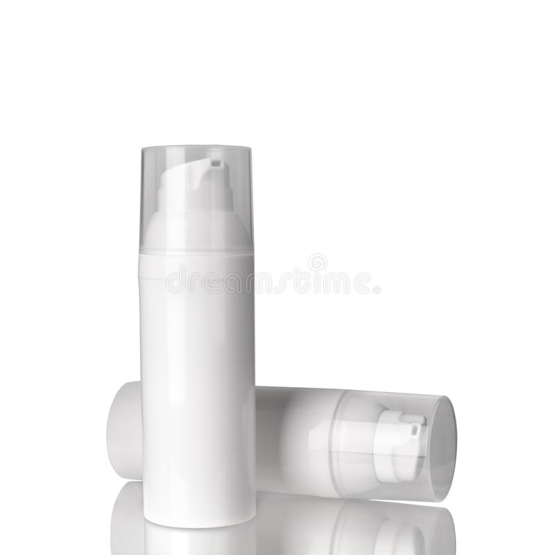 Two white cosmetic cream bottles with dispenser on white background isolated closeup, face cream bottle with transparent caps set. Blank label design template stock photo