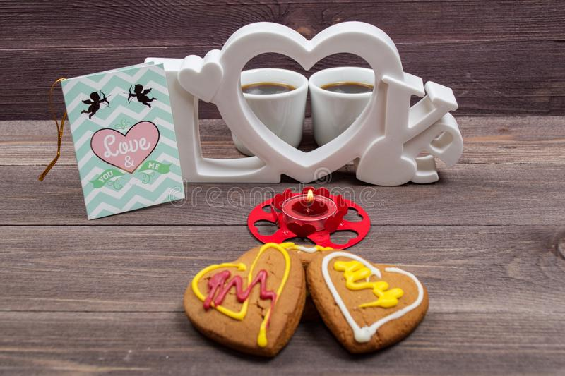 Two white cups of coffee, cookies in the shape of a heart, red candle and a Valentine card on a wooden table. On Valentine's Day royalty free stock image