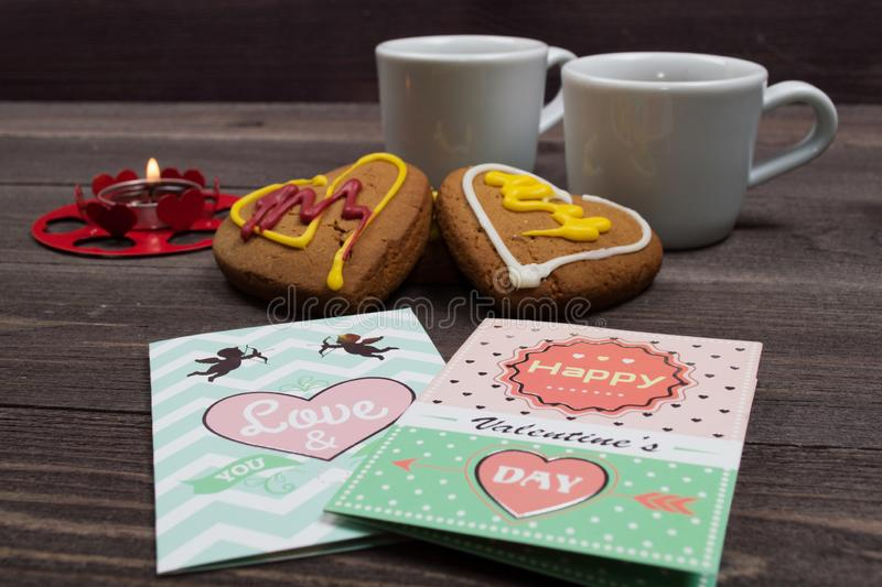 Two white cups of coffee, cookies in the shape of a heart, red candle and a Valentine card on a wooden table. On Valentine's Day royalty free stock photos