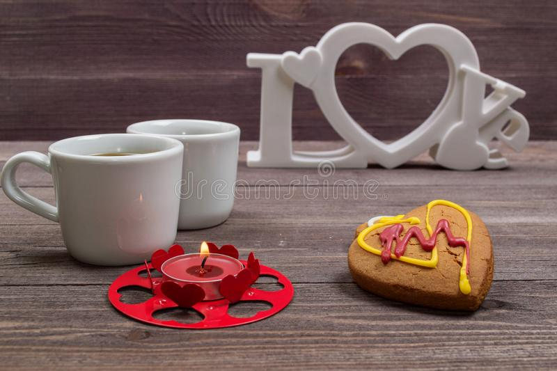 Two white cups of coffee, cookies in the shape of a heart and a red candle on a wooden table. On Valentine's Day stock photo