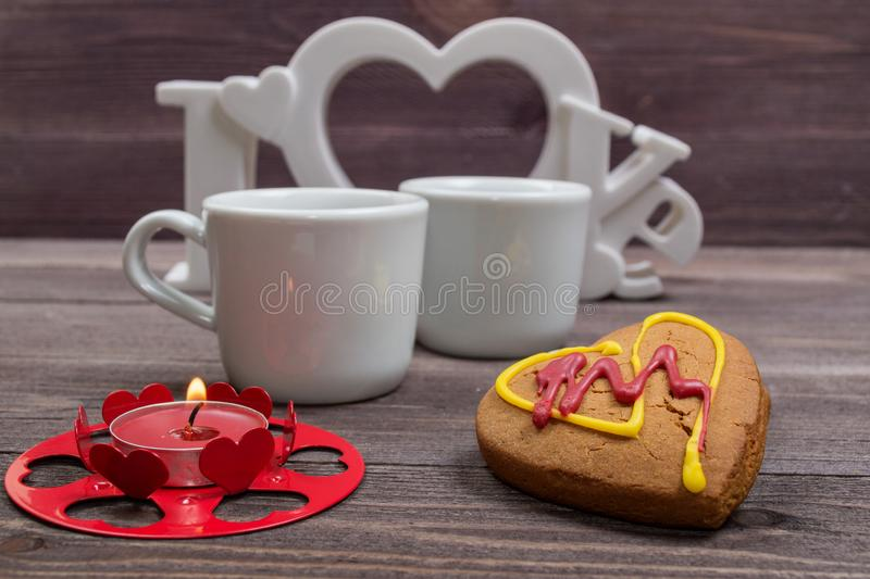 Two white cups of coffee, cookies in the shape of a heart and a red candle on a wooden table. On Valentine's Day stock image