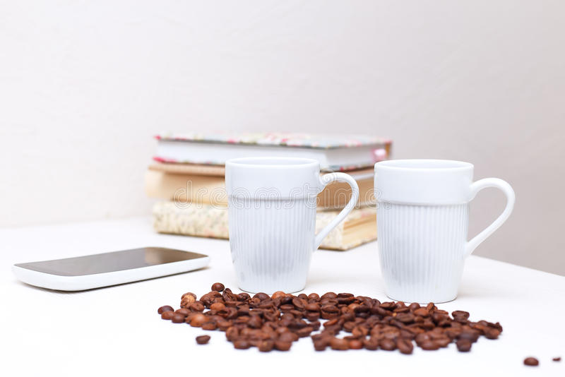 Two white cups of coffee standing on a white table royalty free stock photos