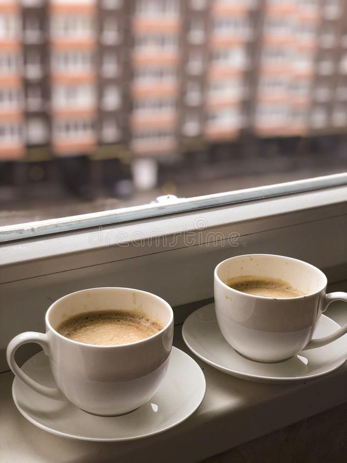 Two white cups coffee on the windowsill. Background, drink, hot, morning, mug, beautiful, christmas, cold, cozy, day, home, nature, season, snow, tea, view royalty free stock photography