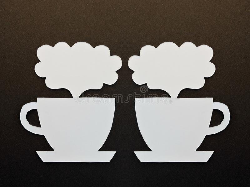 Two white cups cut from paper. Two beautiful white cups cut from white paper on black background royalty free stock photos