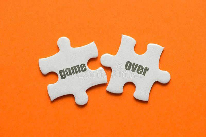Two white details of puzzle with text Game Over on orange background, close up.  royalty free stock photos